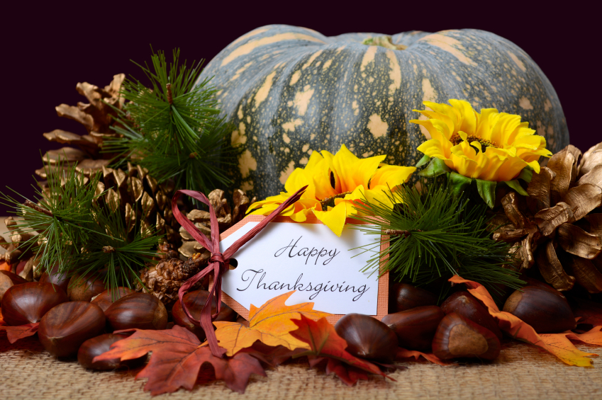 Happy Thanksgiving Pumpkin in Rustic Setting on burlap covered table with greeting message.