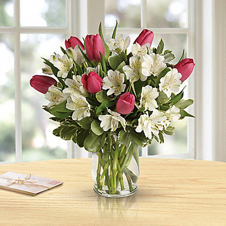 pink tulips and white flowers in clear vase