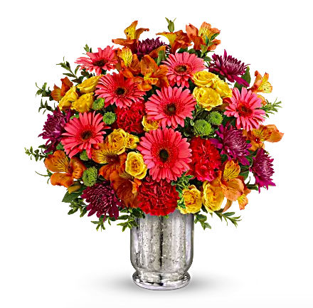 bright pink, orange, and yellow flowers in silver mercury vase