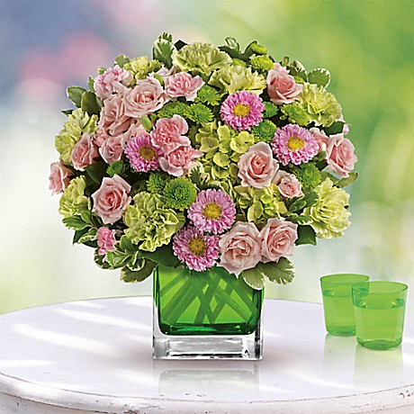 pink and green flowers in green cube vase