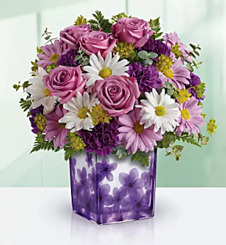 purple and white flowers in violet cube vase
