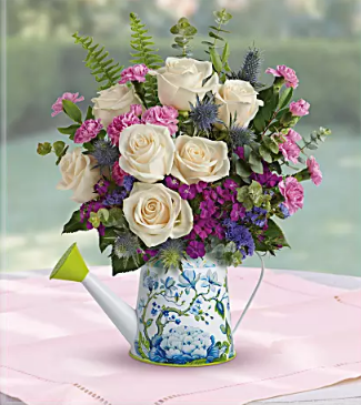 purple and white flowers in blue watering can vase