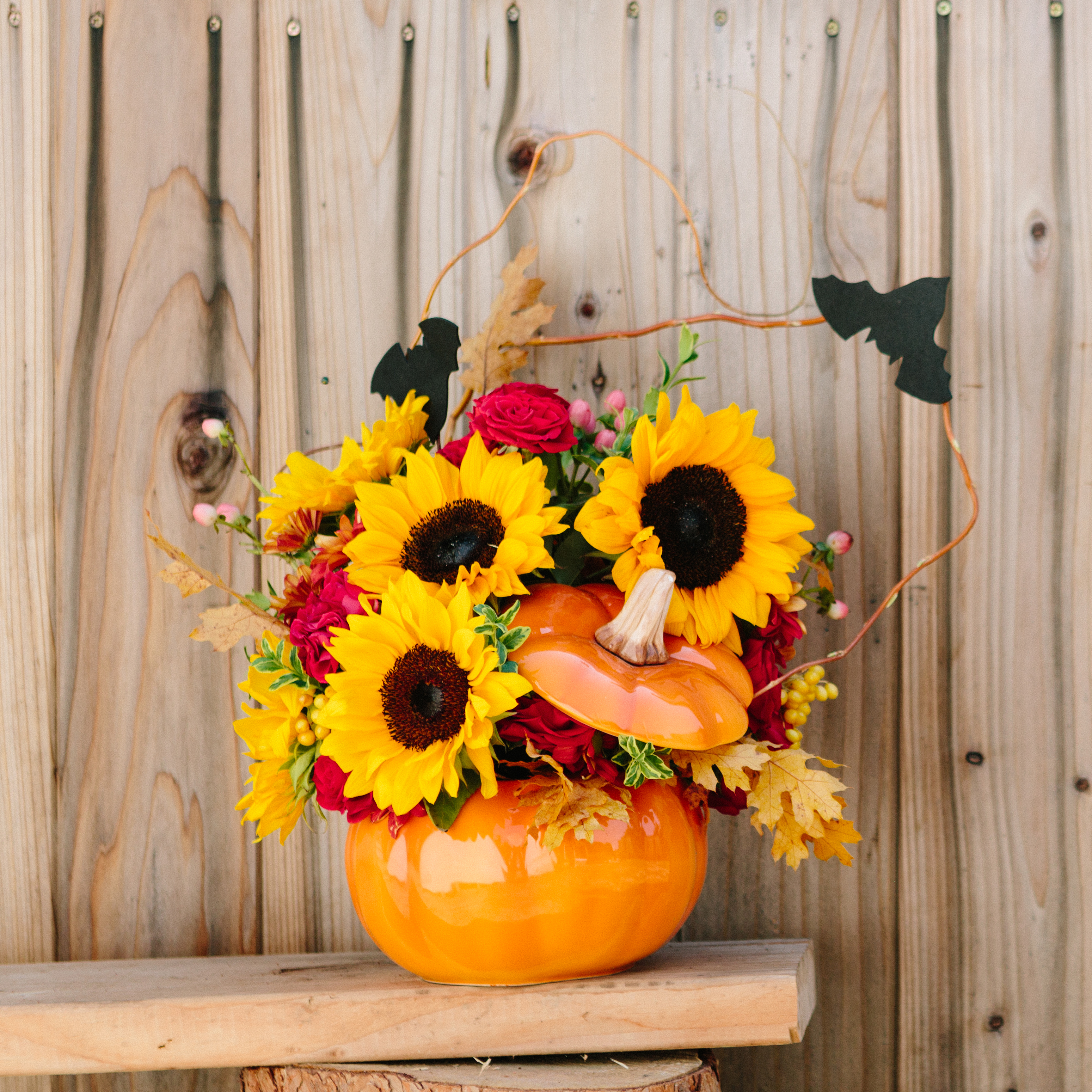 Teleflora Trick or Treat Bouquet. Sunflowers, roses, and mum in a glass pumpkin with bats.
