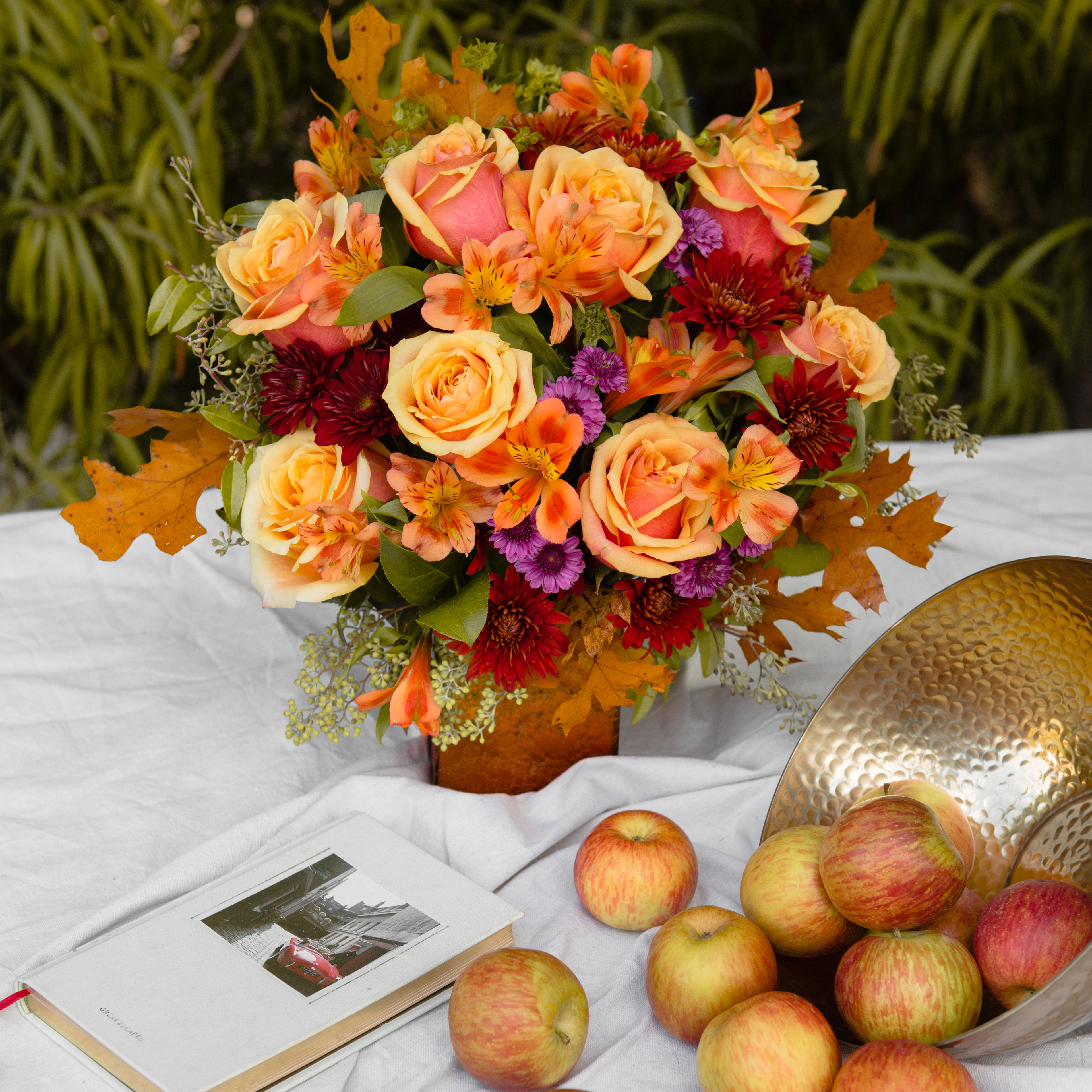 Orange roses with leaves and more on table with apples