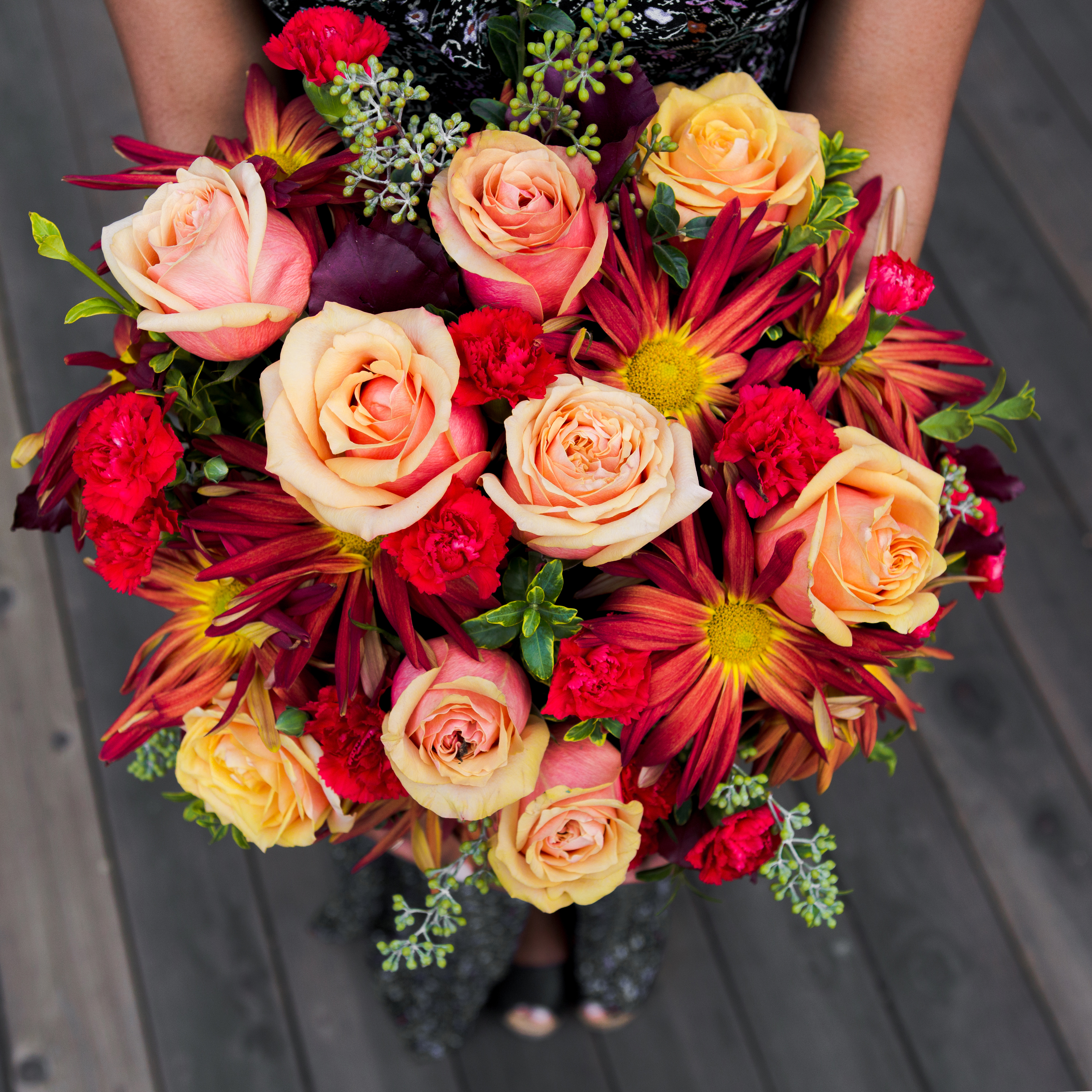 orange roses, carnations, and mums in burnt orange crock