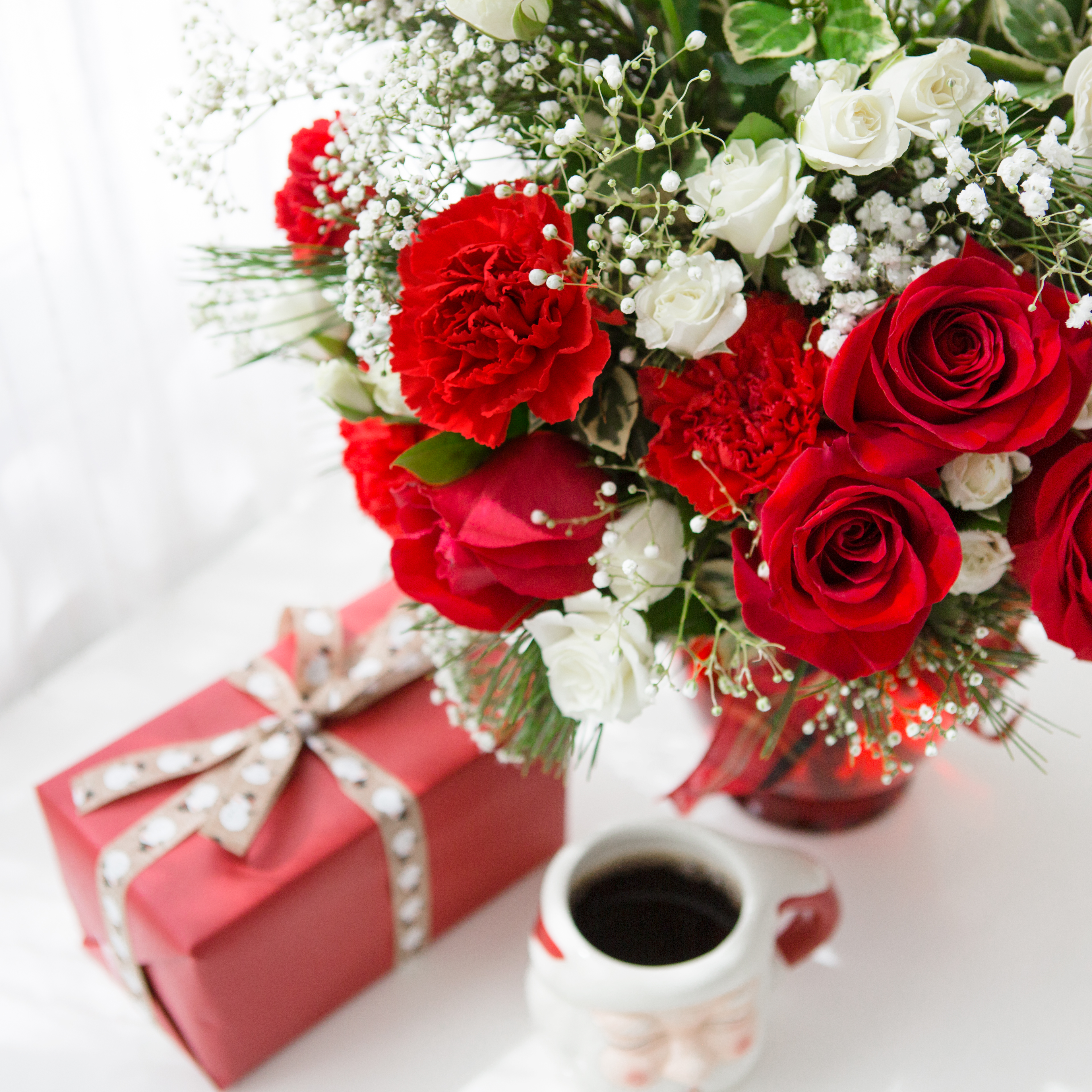 red and white flowers in red vase on table with present and coffee