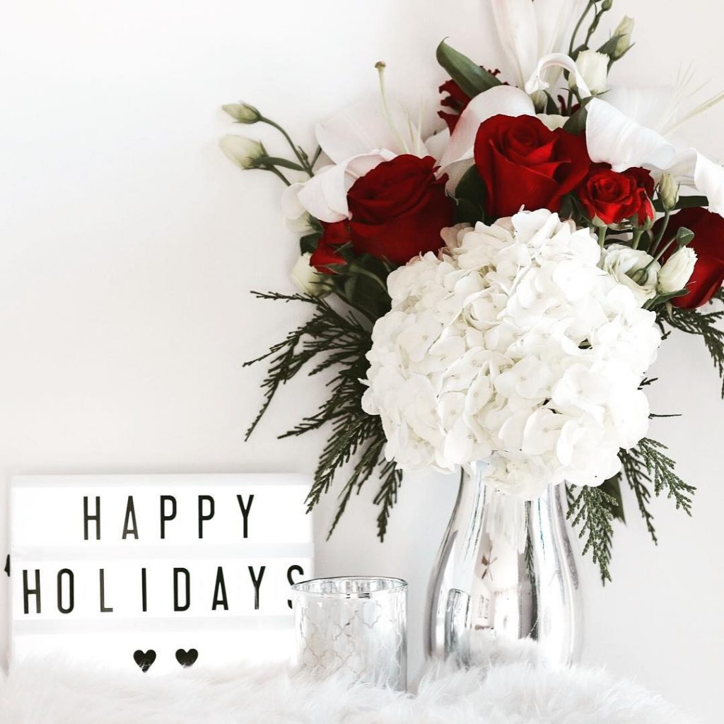 White hydrangea and red roses in silver vase with happy holiday sign