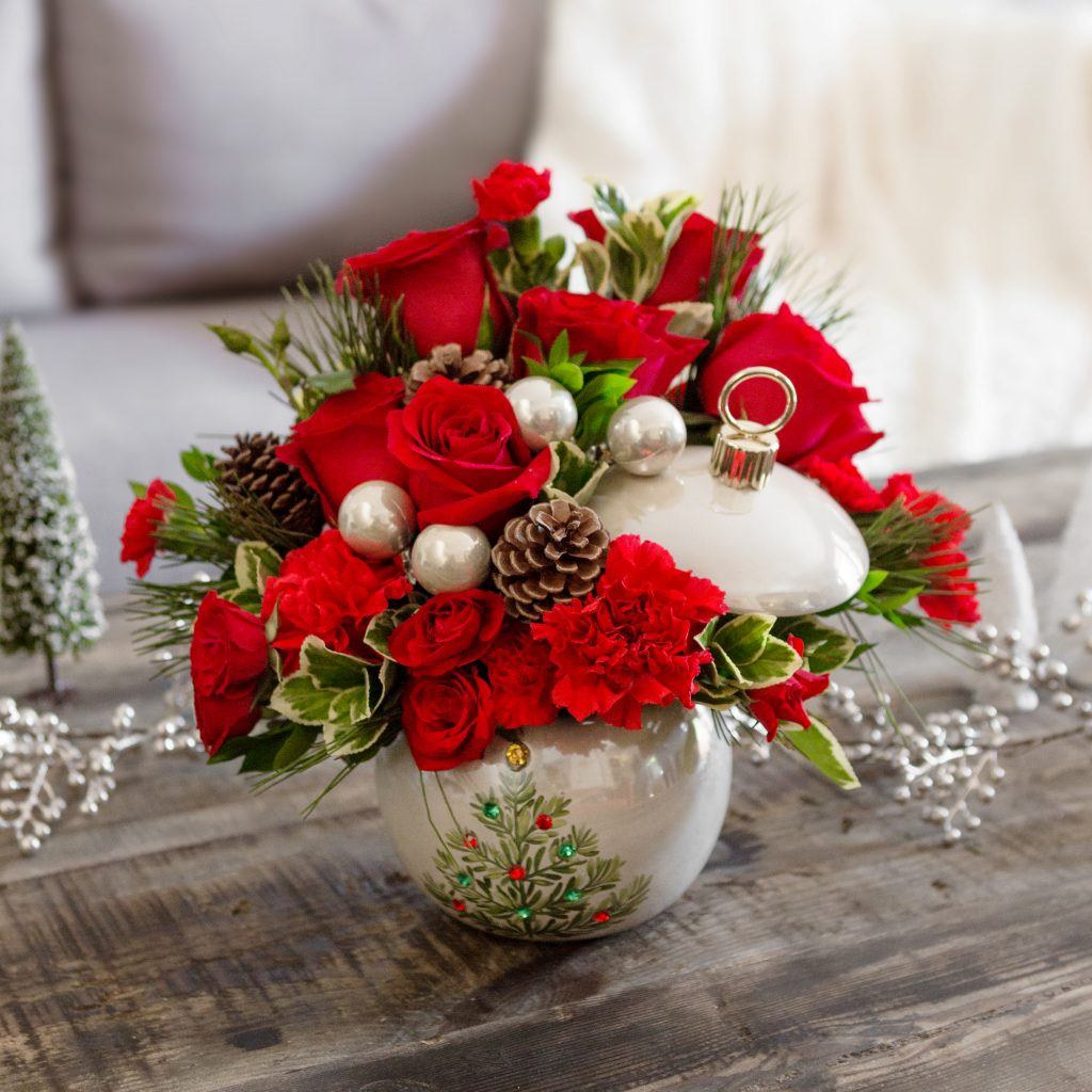 Pearl ornament filled with red flowers and greenery