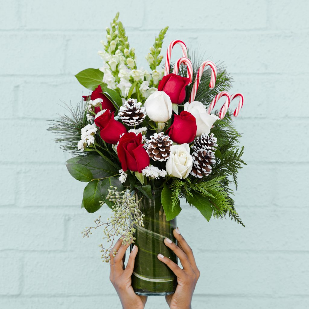 Red and white roses holiday greenery and candy canes in a vase