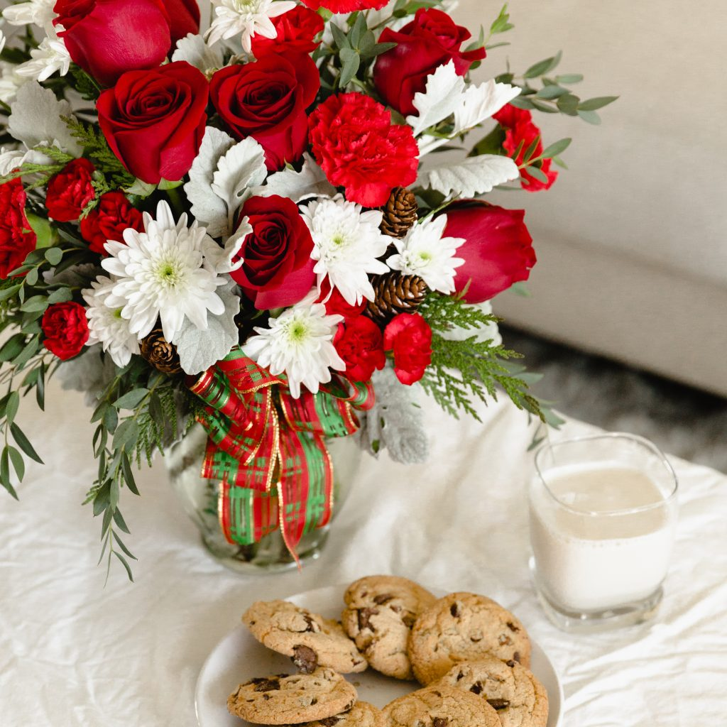 Red roses and white flowers in clear vase with a ribbon next to cookies