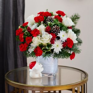 Red and white flowers with greenery in white cube polar bear vase