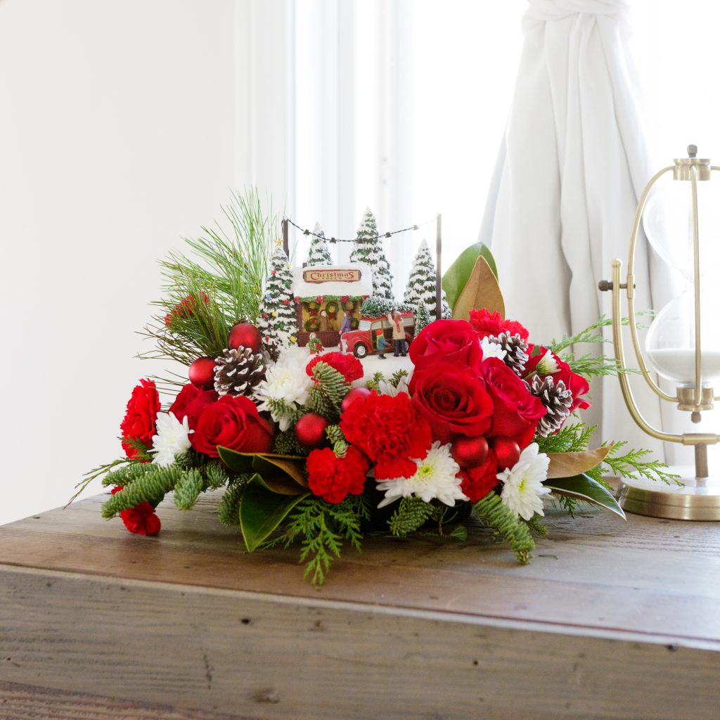Hand-painted holiday resin surround by red and white flowers with greenery