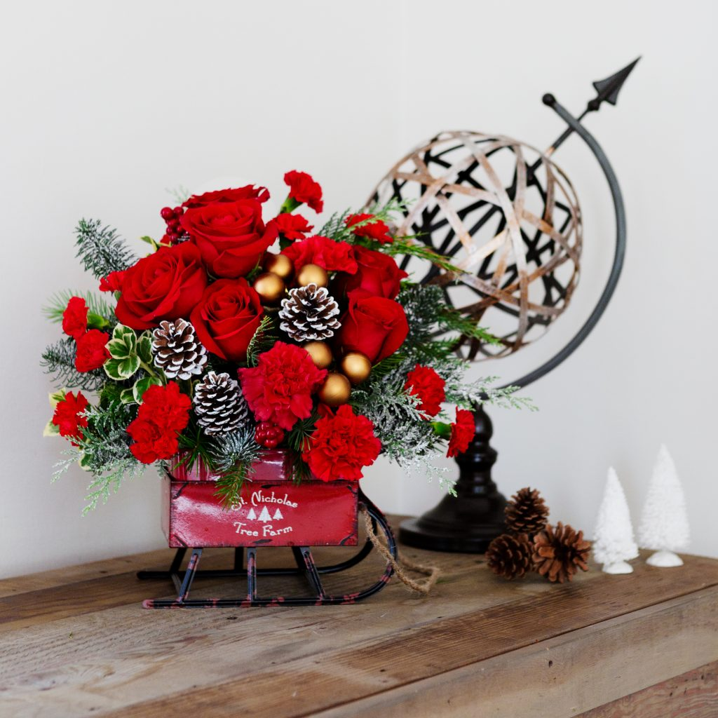 vintage sleigh filled with red flowers and pinecones