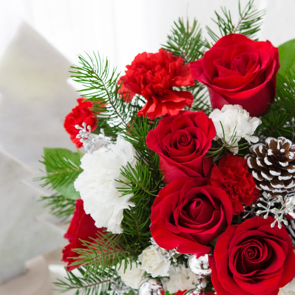 Closeup of red roses, pinecones, and greenery