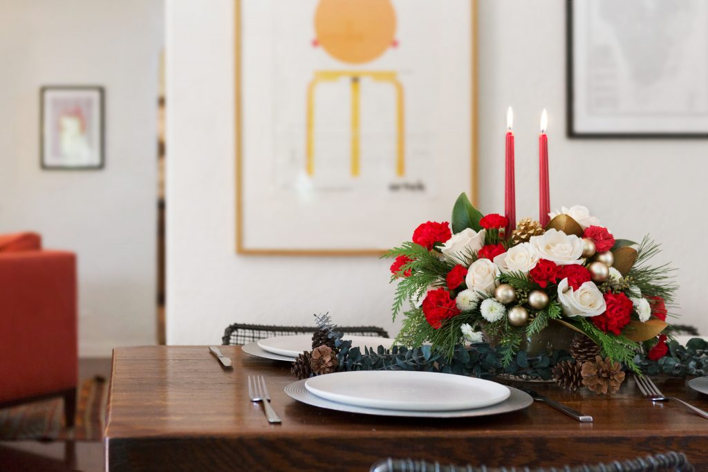 White, red, and green flower centerpiece on wood table