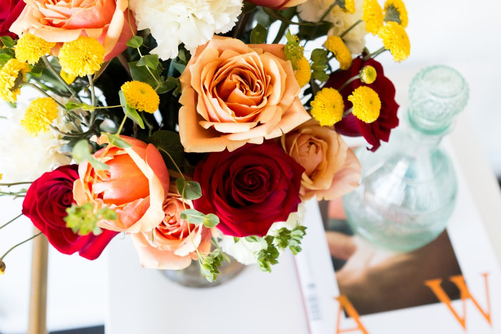 red and orange roses with greenery in a vase