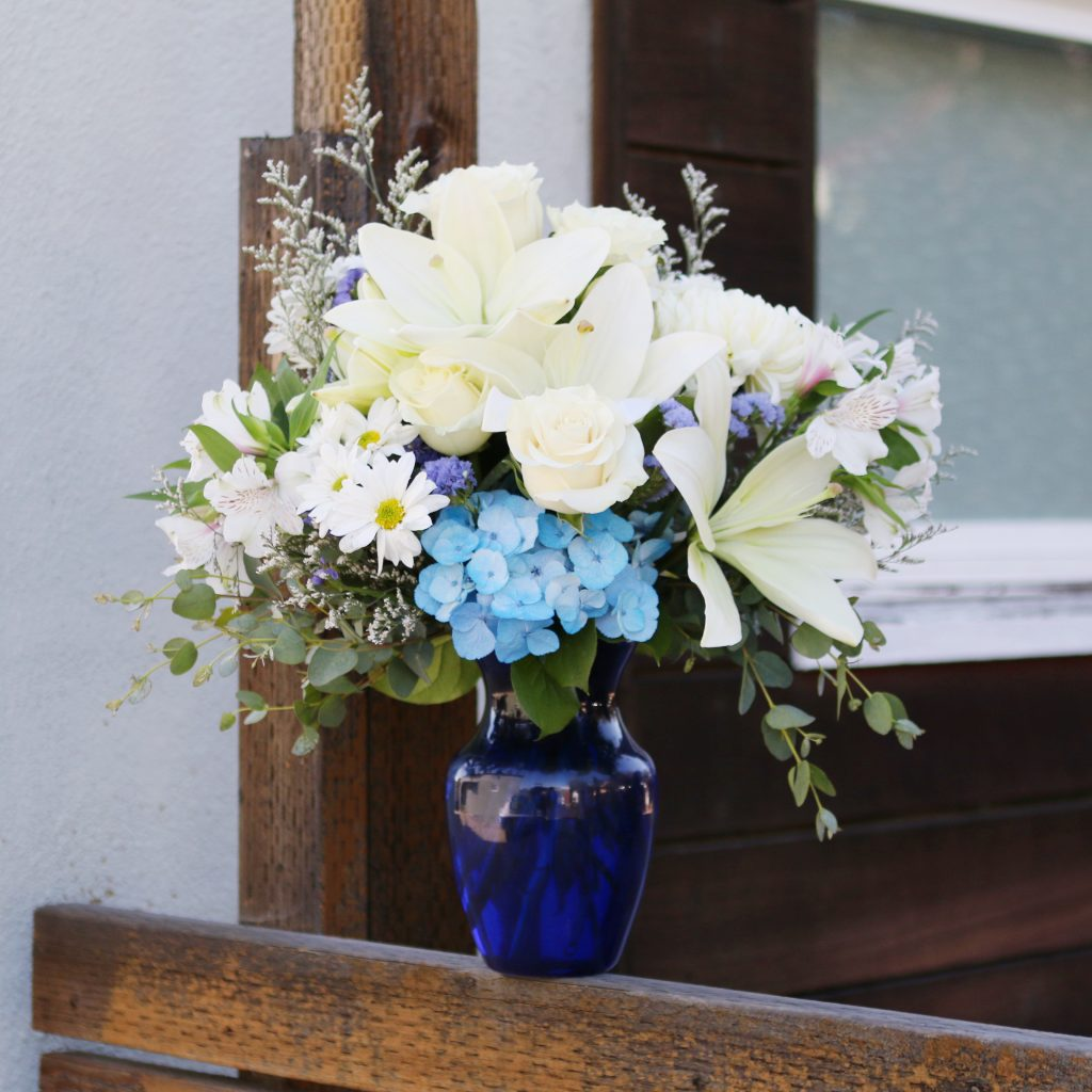 Blue hydrangea and white lilies in blue vase