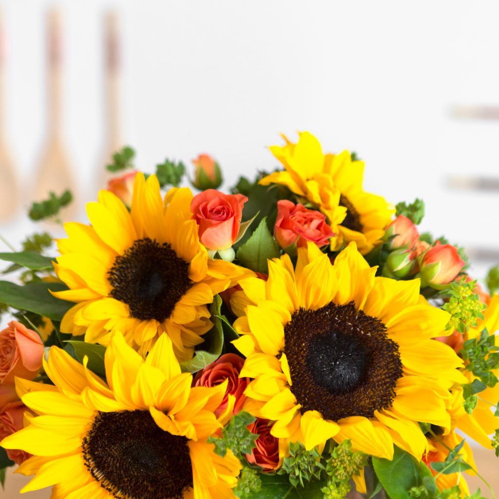 yellow sunflowers with orange spray roses in clear vase
