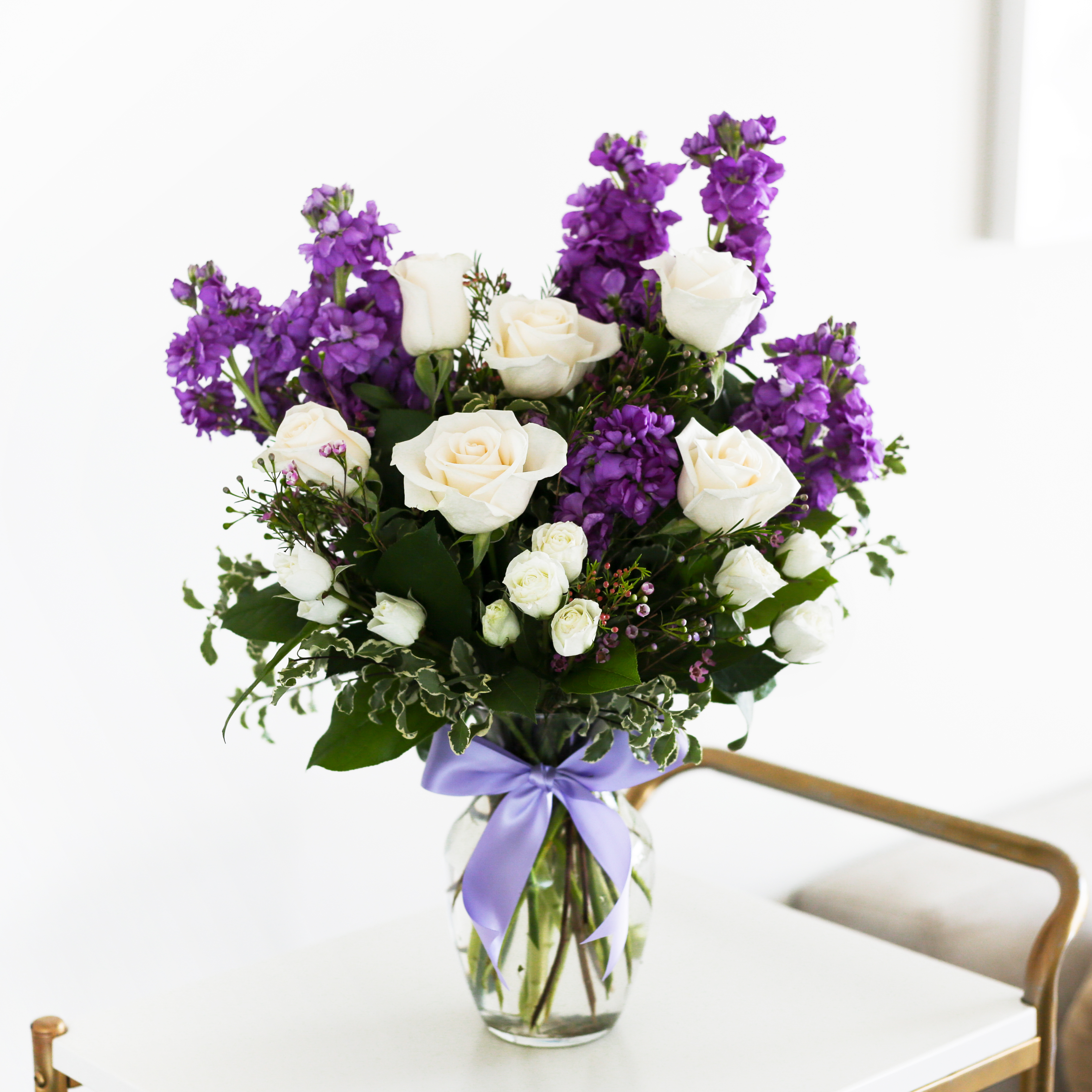 white roses and lavender stock in vase with purple bow