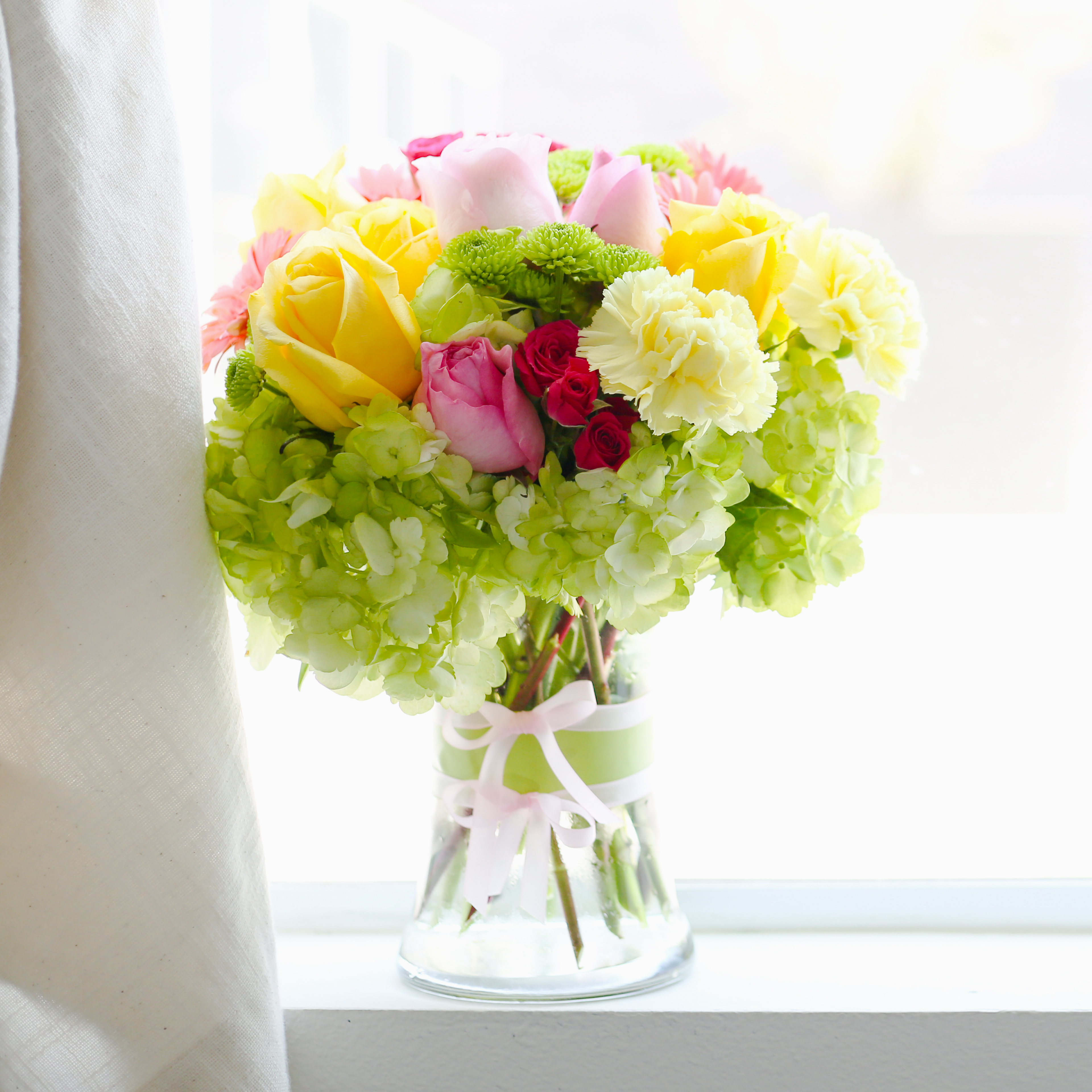 hyrdrangeas, roses, carnations and more in clear vase in the window