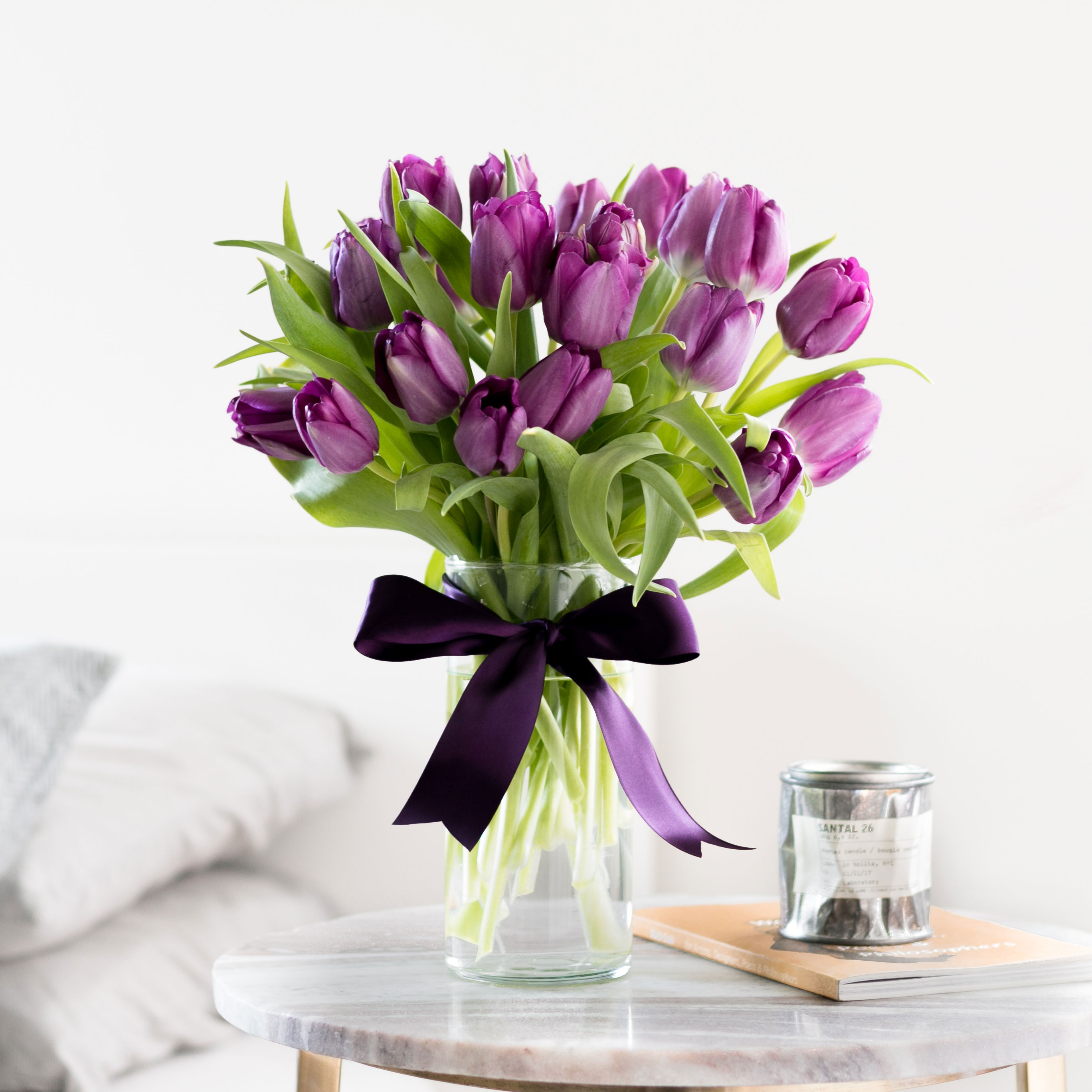purple tulips in vase with purple ribbon