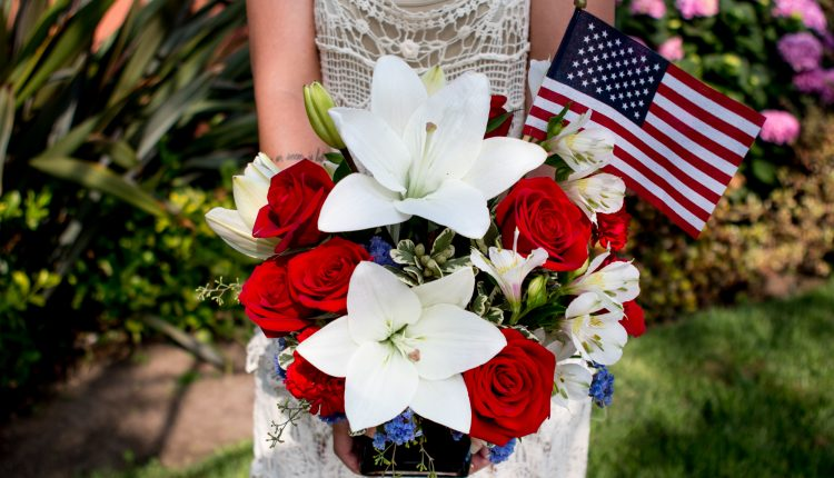 white lilies and red roses in a blue vase with American flag