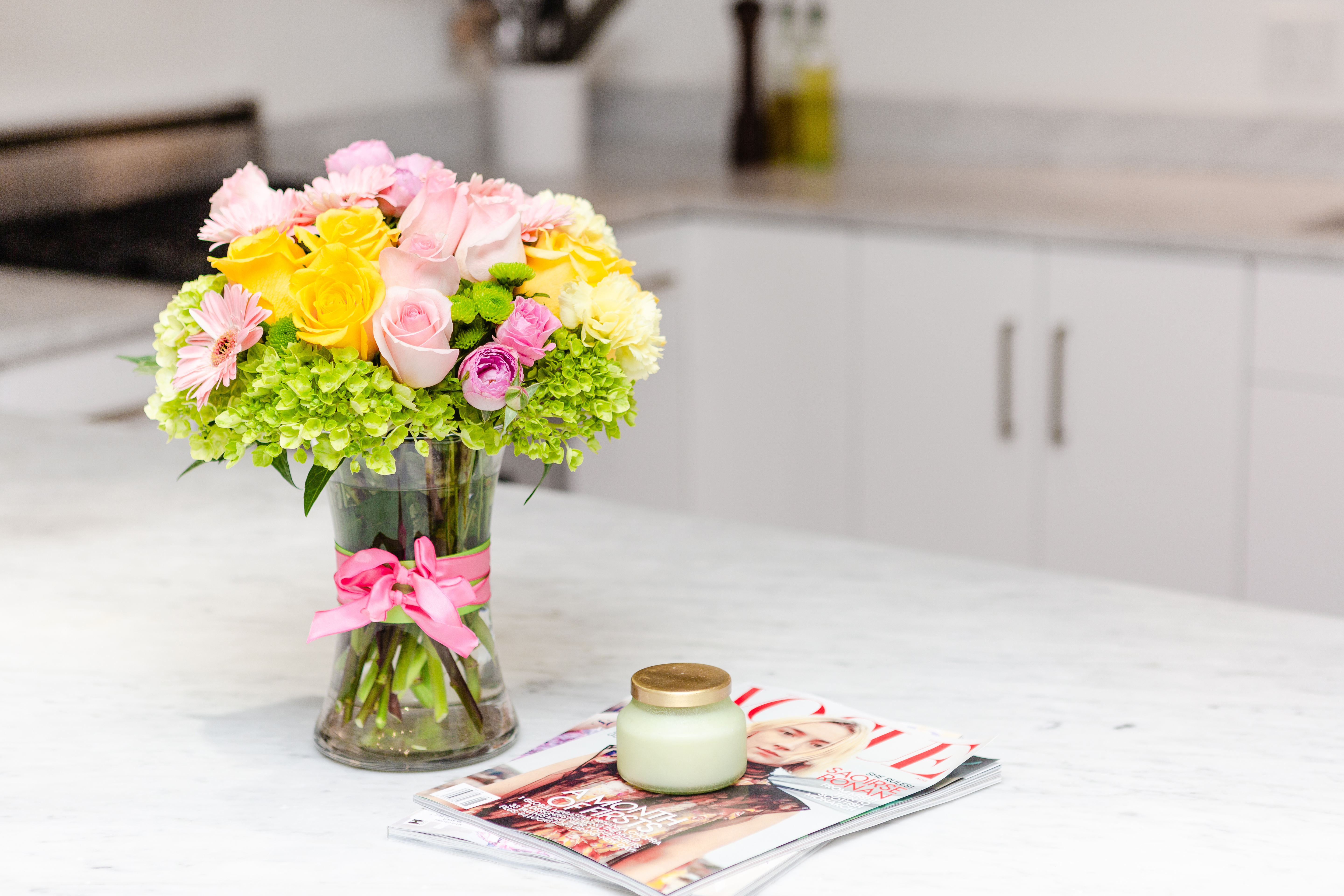 pink and yellow roses with green hydrangea in clear vase on table with magazines
