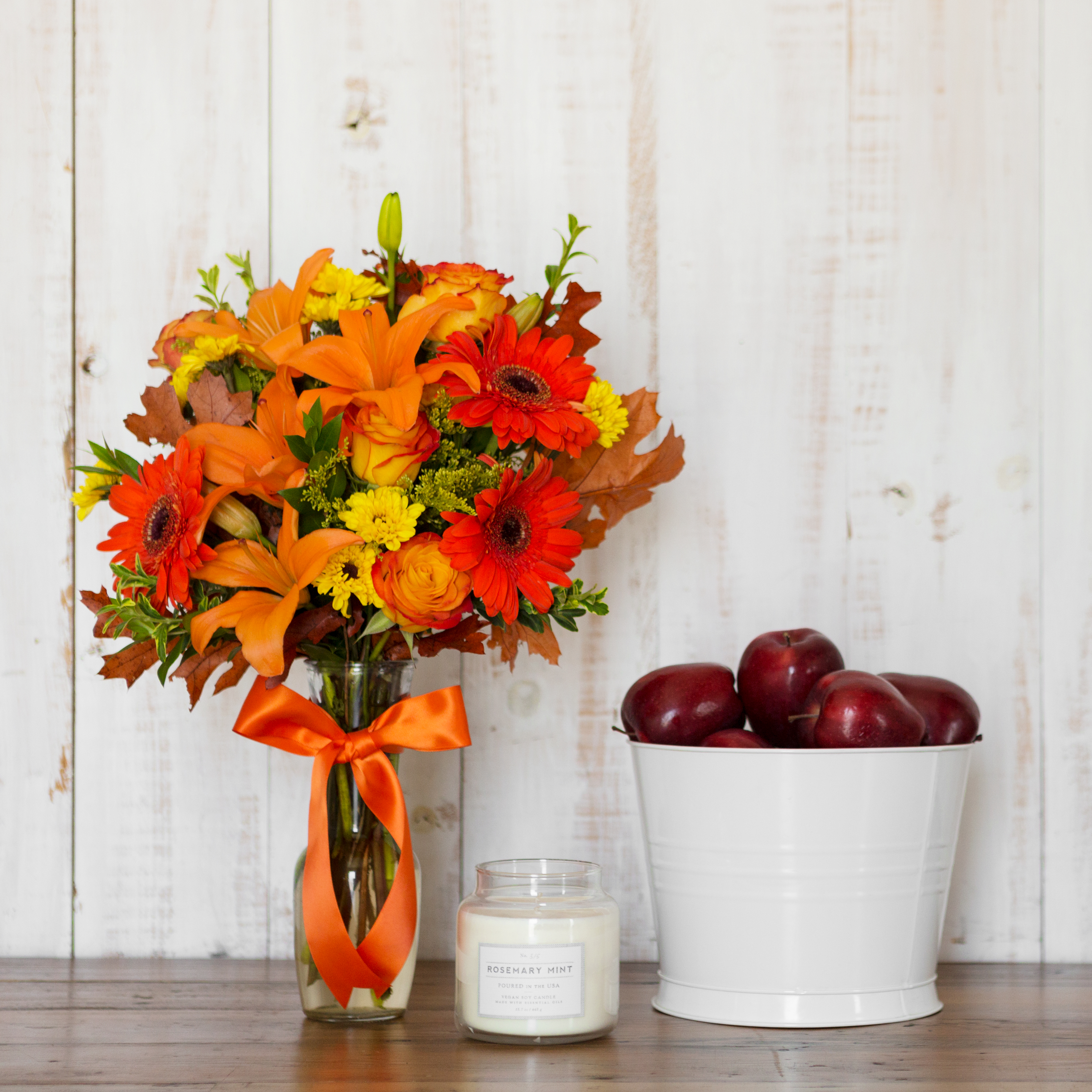 Orange lilies, red carnations, leaves, and greenery in clear vase with orange ribbon on table with candle and apples