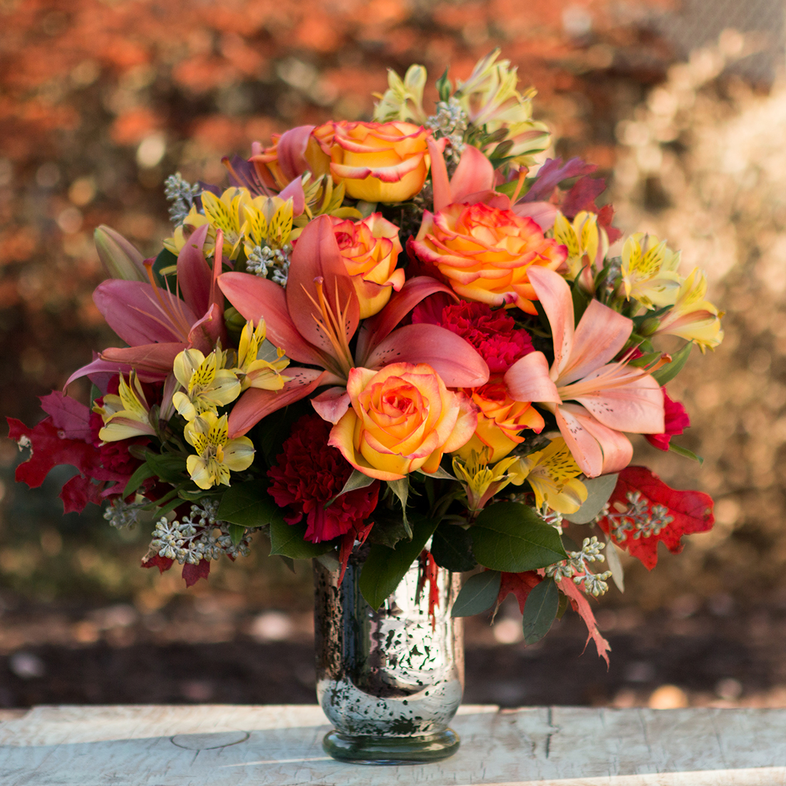 Oranges roses, pink lilies, and greenery in silver vase with fall foliage in the background
