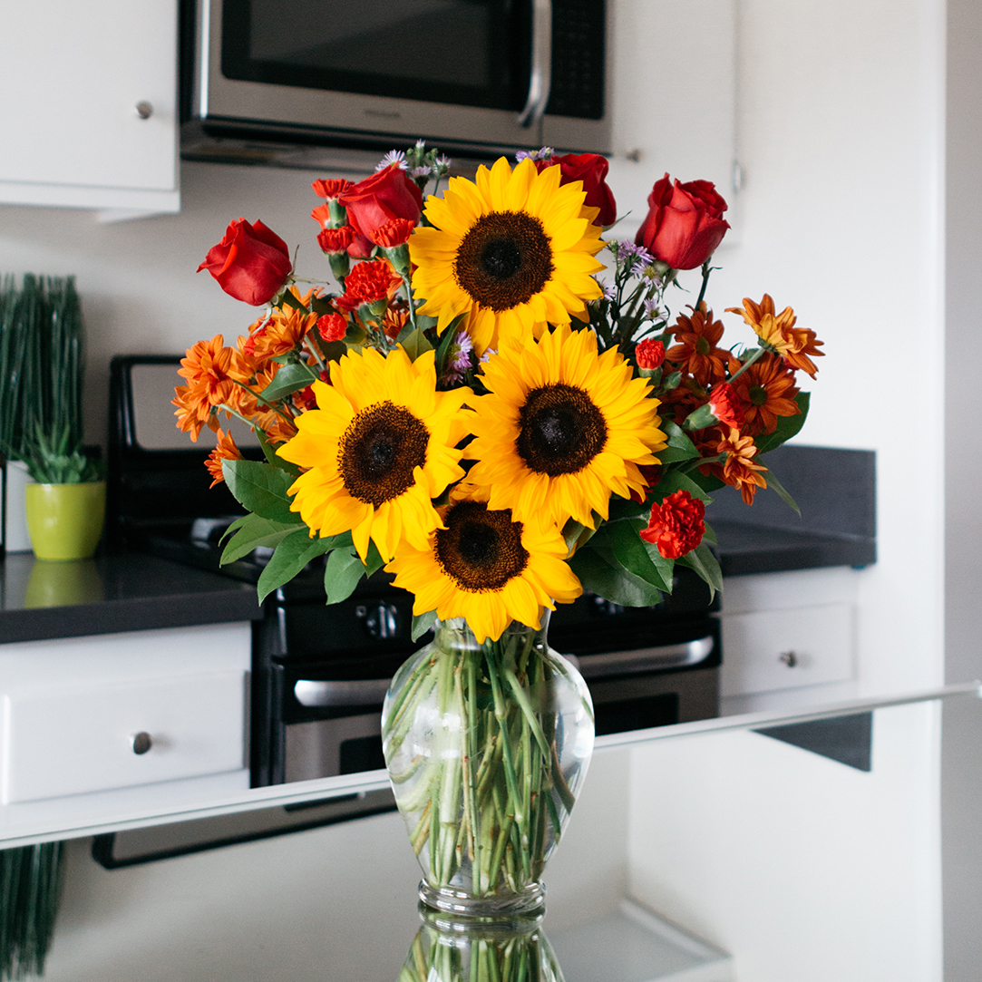 Sunflowers, red roses, and greenery in a clear vase on kitchen counter