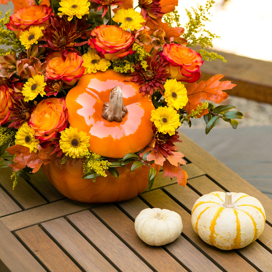 Orange roses, yellow carnations, mums, and more in a pumpkin vase with gords