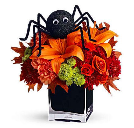Orange lilies, orange roses, green mums, and more in a cube with a spider decoration