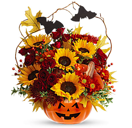 Orange pumpkin vase filled with sunflowers, roses, fall foliage, and more with bat decorations
