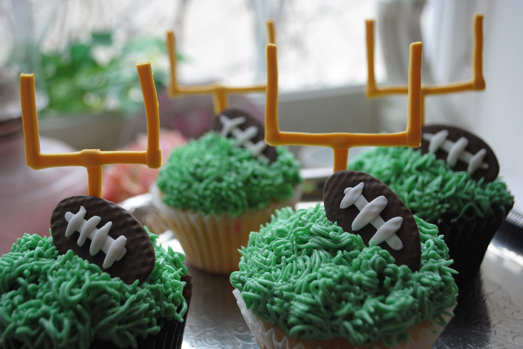 Cupcake decorating with a football and grass