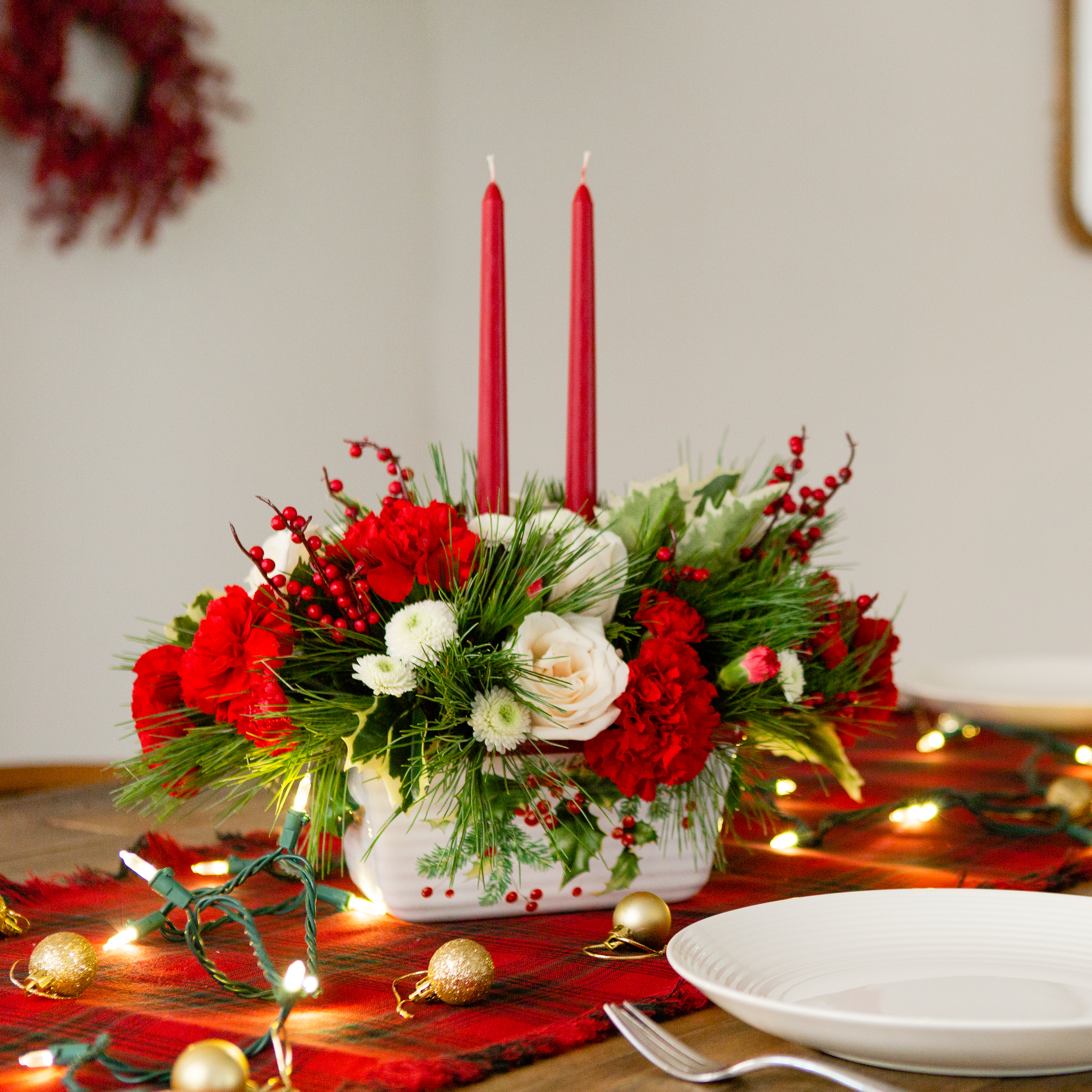 Red carnations and white roses accented with greenery fill a ceramic dish with holly accents