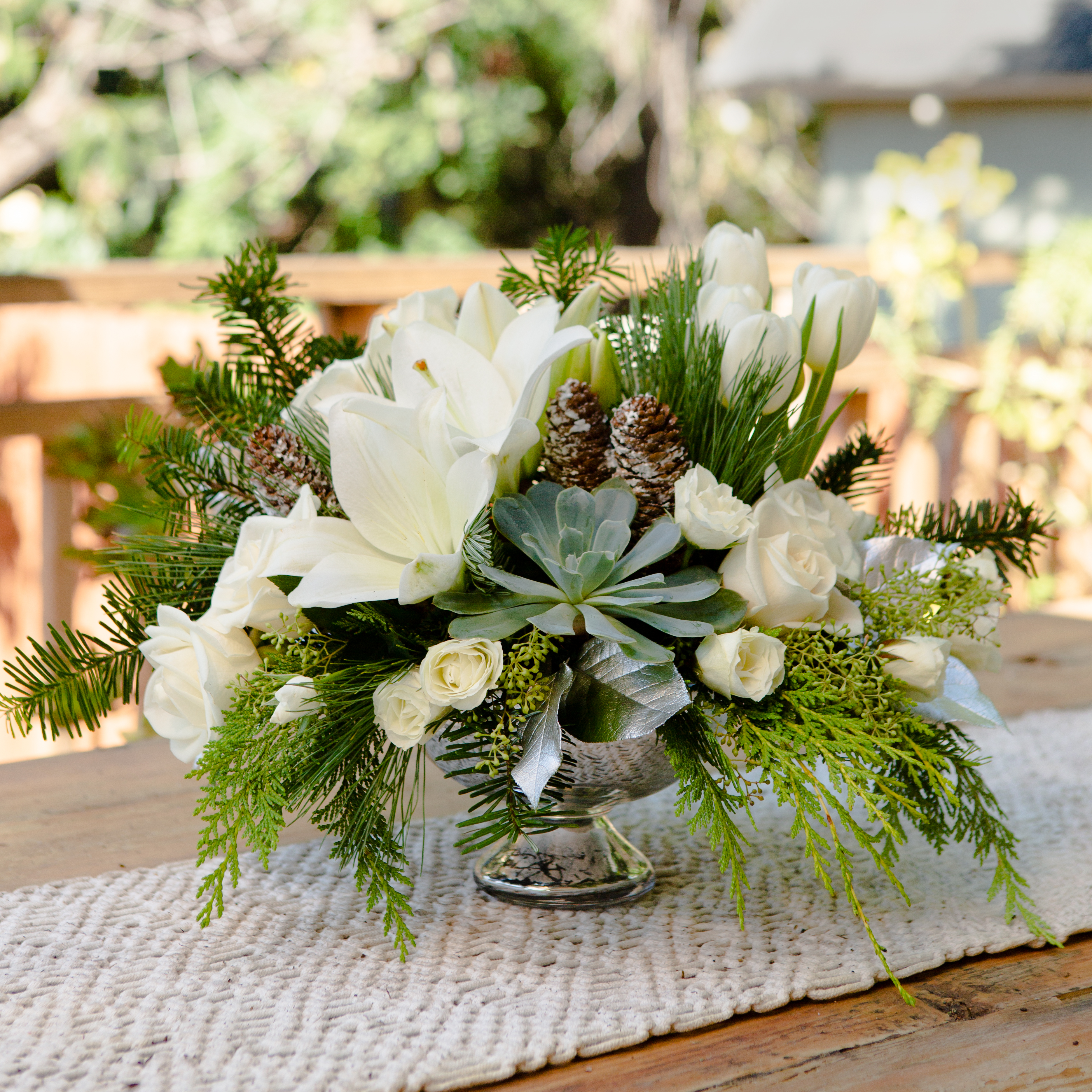 White lilies, white roses, succulents, and greenery fill a fill centerpiece and are accented with pinecones
