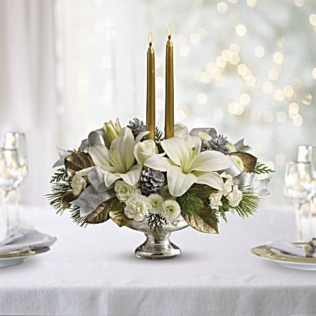 White lilies, white carnations, and white mums are accented with silver and gold and make up a beautiful table centerpiece