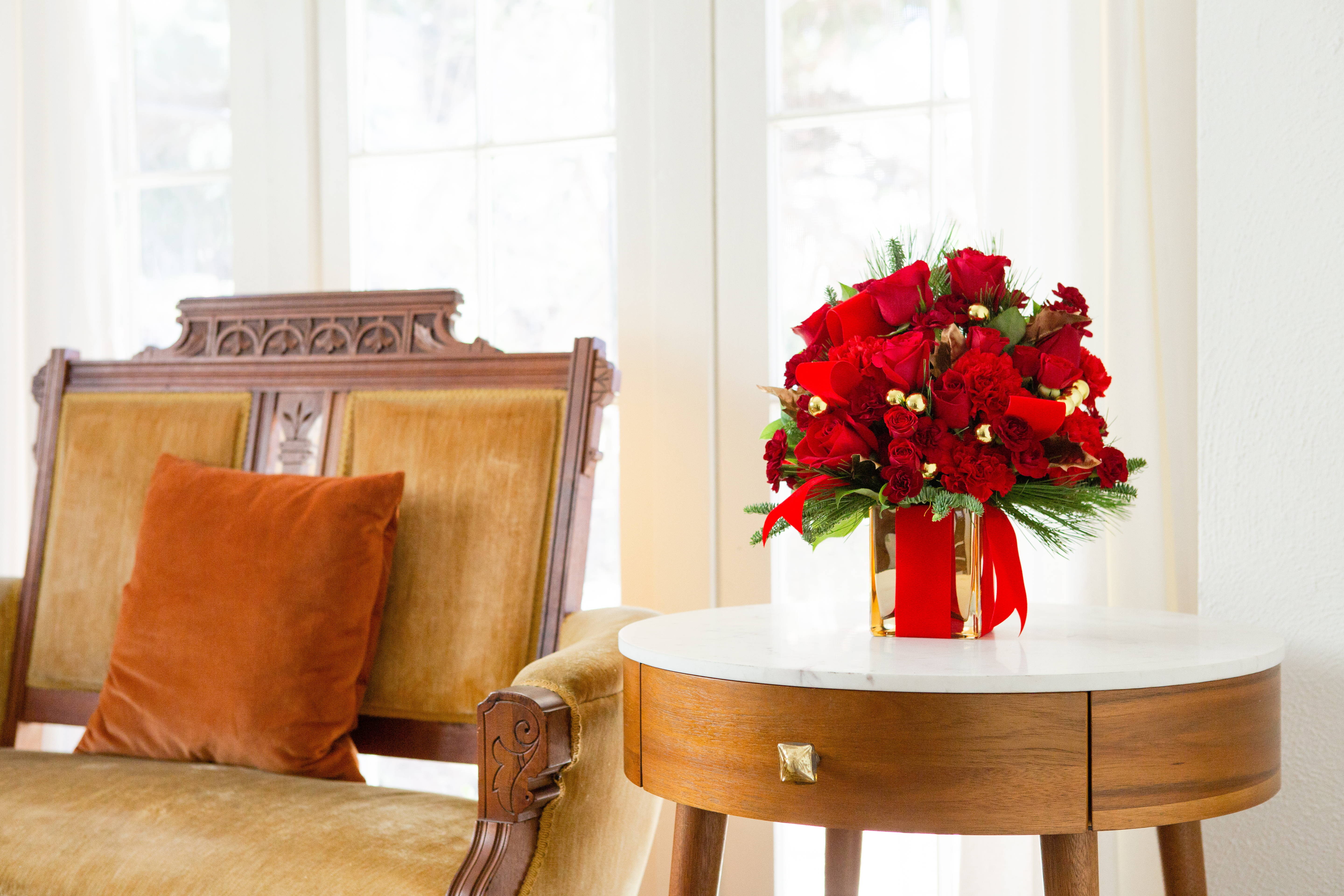 red holiday flowers fill a gold cube wrapped in red ribbon sitting on side table