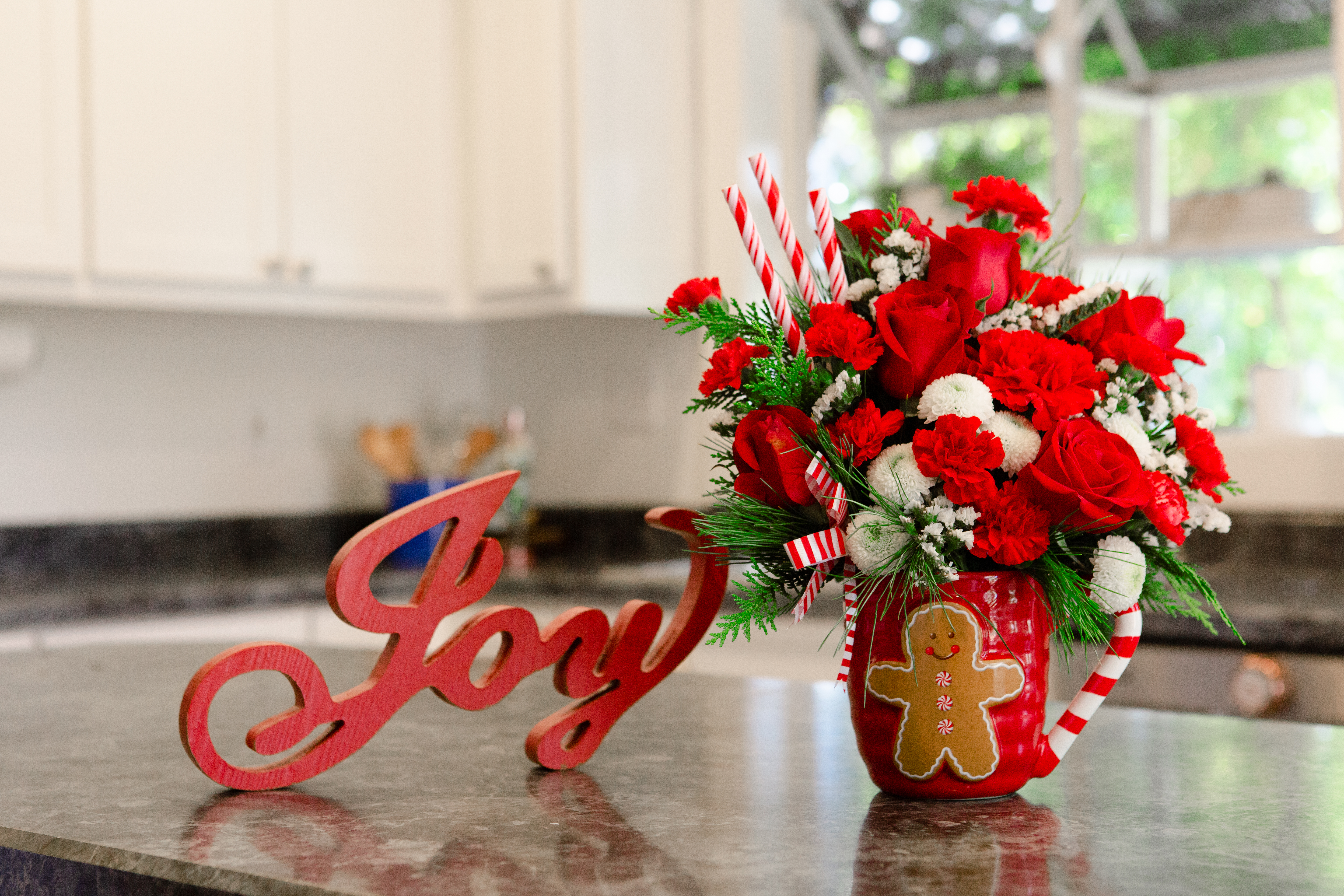 Red gingerbread coffee mug filled with red roses, white mums, red carnations, greenery and more next to a joy wooden letters.