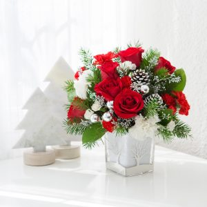 Red and white flowers with greenery in silver and white vase