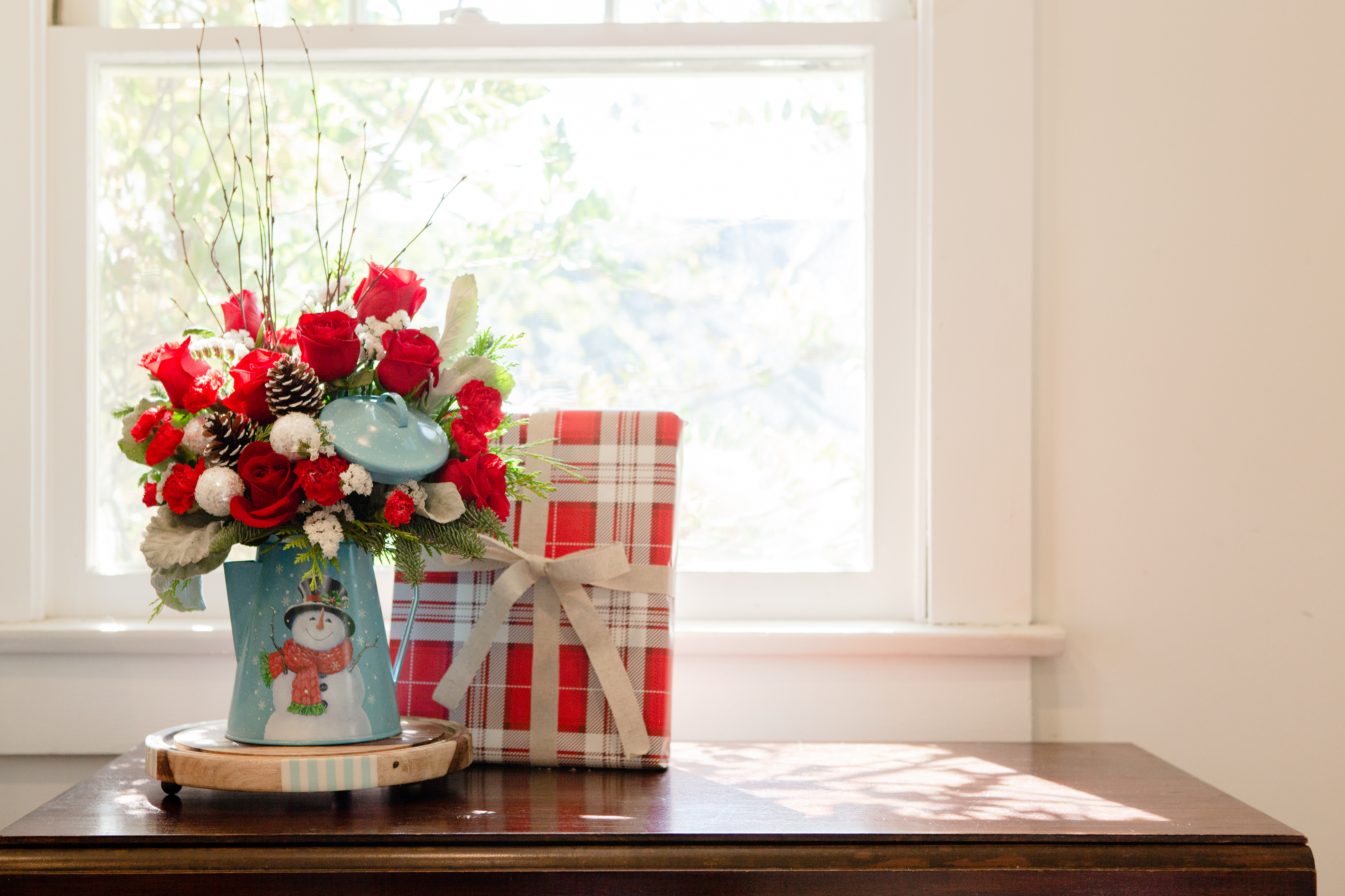 Red roses, red carnations, and greenery in a blue snowman watercan vase with a present