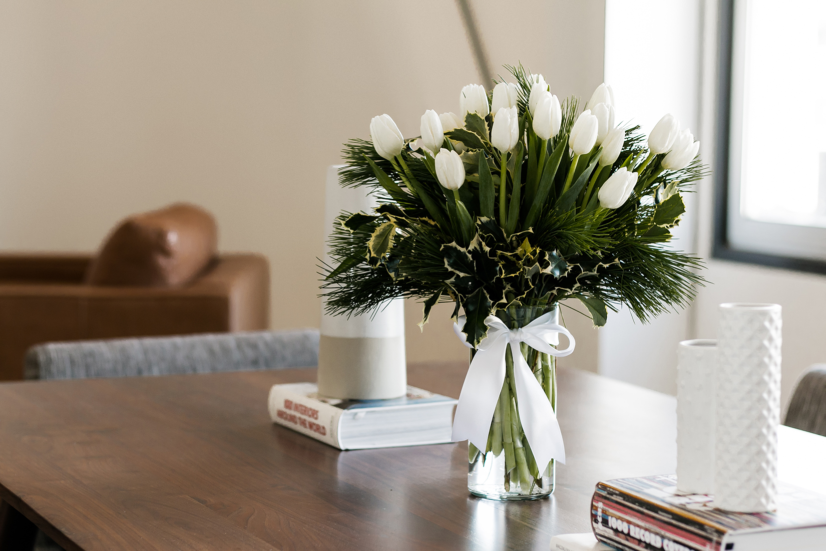 White tulips with pine accents in a clear vase with a white ribbon on a wooden table