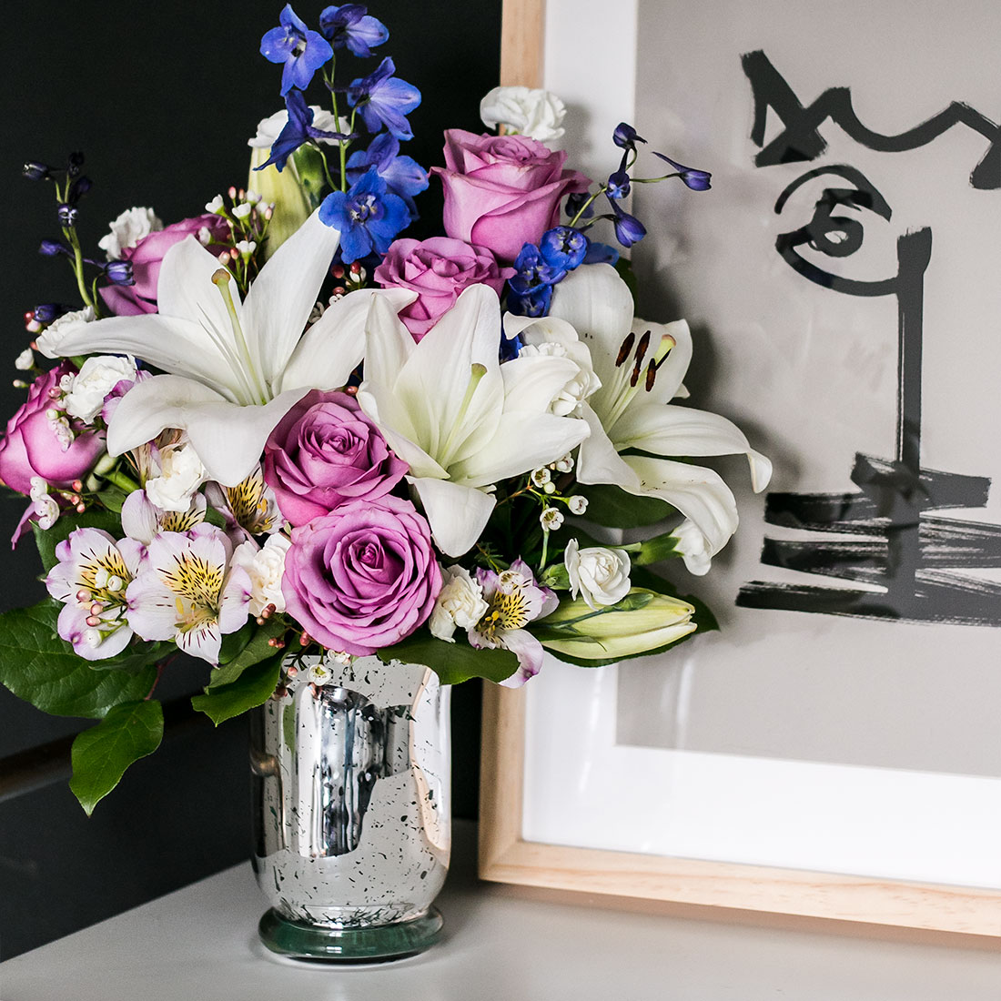 White lilies, purple roses, white mums, and more fill a silver vase sitting next to a picture