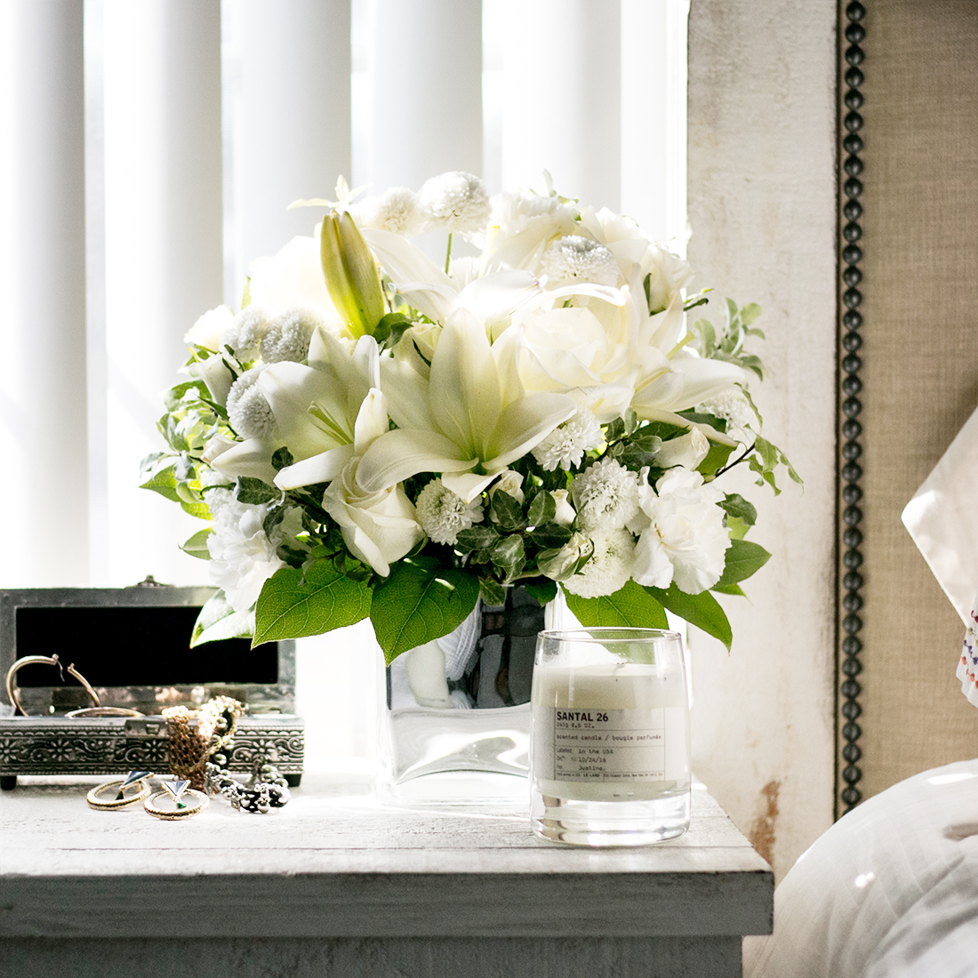 White lilies and white mums surrounded by greenery in a clear cube vase