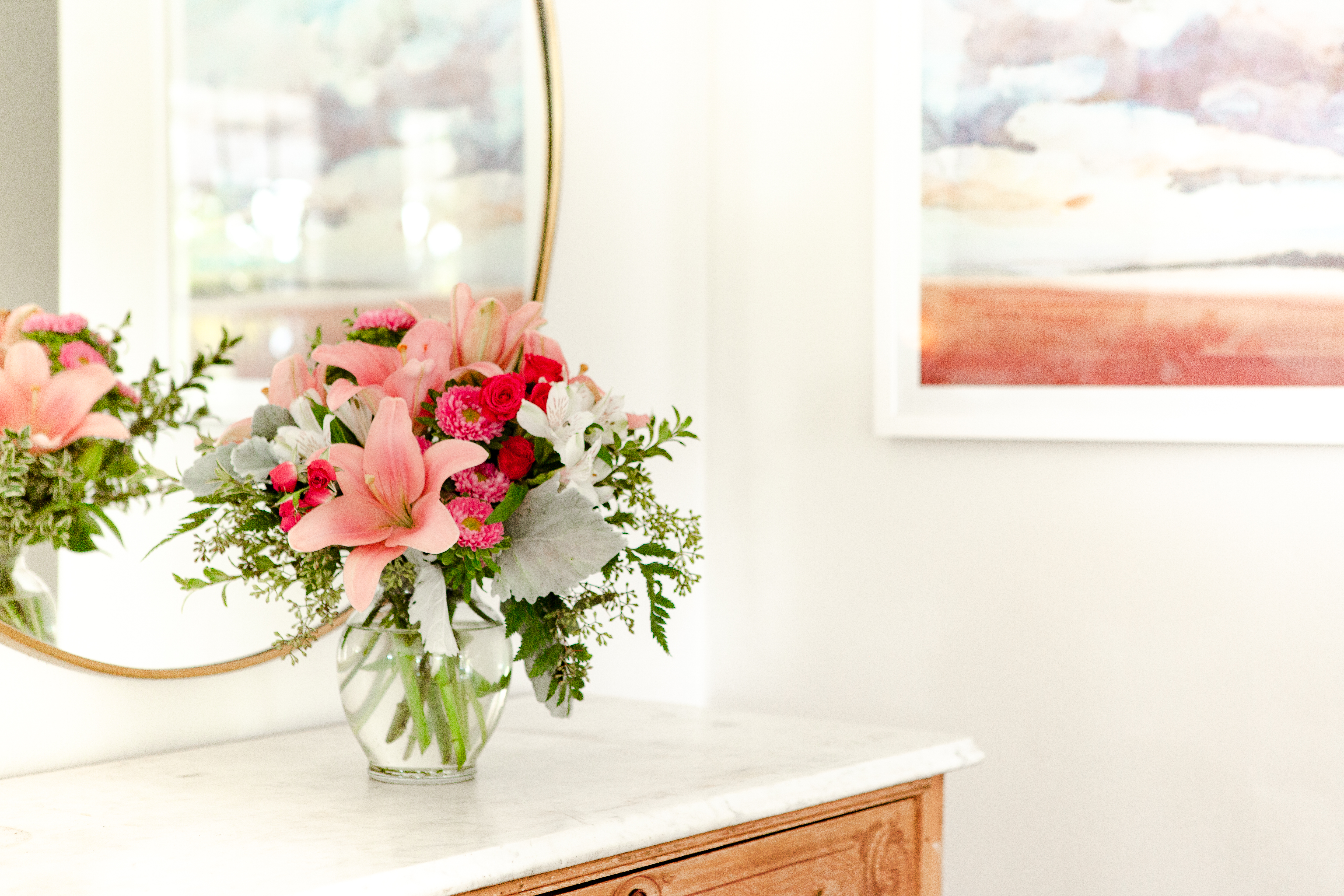 Pink lilies, pink asters, alstromeria, and dusty millar fill a clear vase on dresser next to mirror