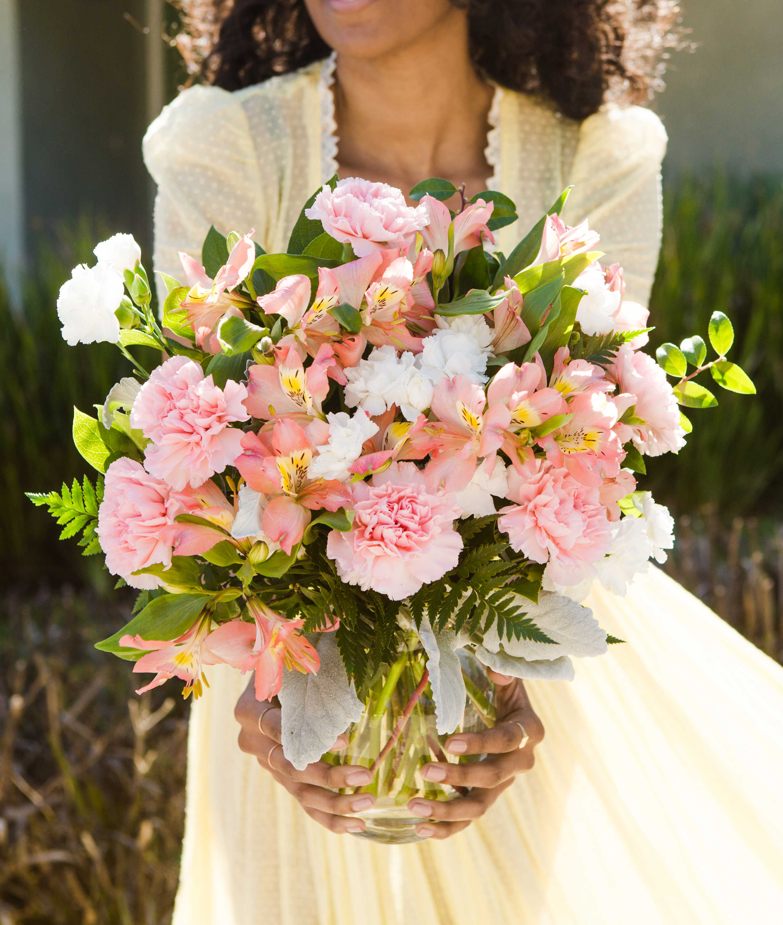 Pink and white carnations surrounded by dusty miller and greenery in a clear vase in girls hands