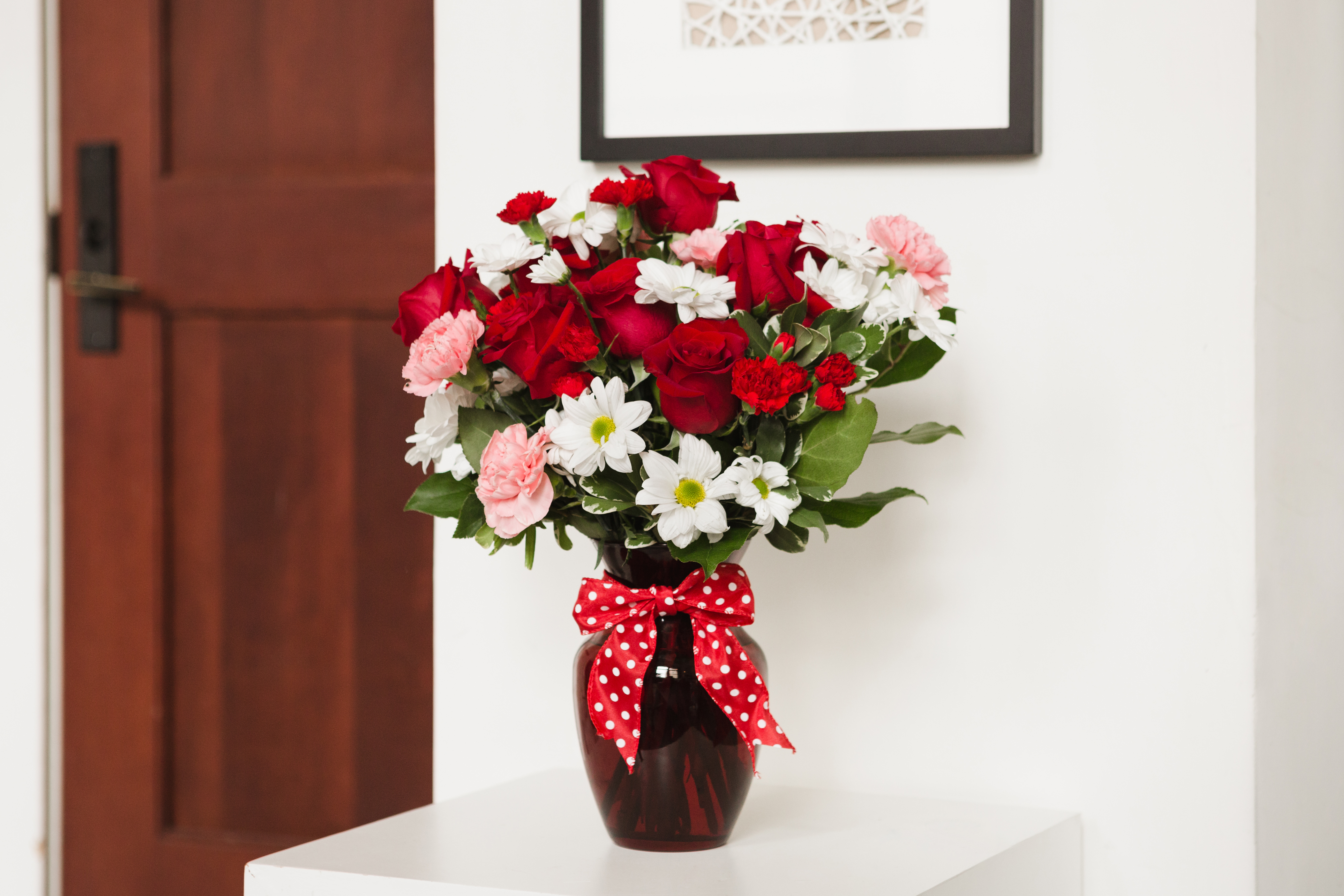 red roses, pink carnations, white daisies, and more in a red vase on a white table