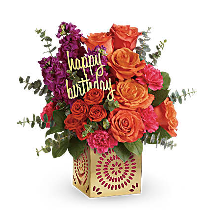 orange roses, pink carnations, purple static, and more in a gold cube vase