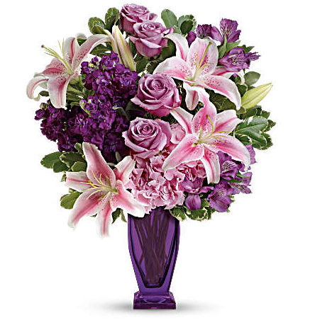 Lilies, purple roses, alstromeria, and more in a purple vase