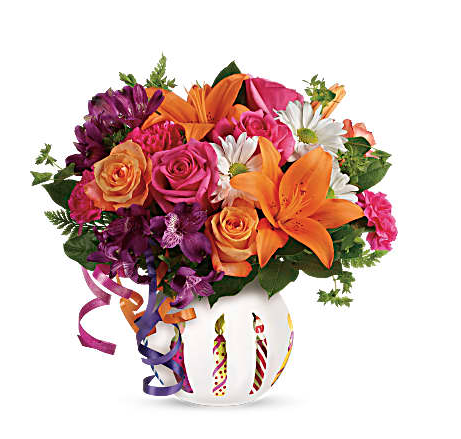 Orange lilies, pink roses, purple alstromeria, and more in a white birthday candle bowl